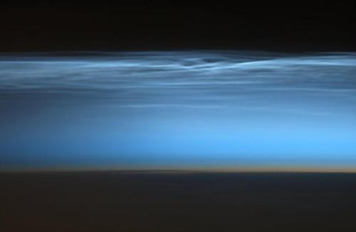 Noctilucent clouds. They form at high latitudes, at altitudes in excess of 75 km. They are rarely visible from the ground.