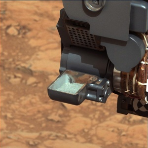 This image from NASA's Curiosity rover shows the first sample of powdered rock extracted by the rover's drill. The image was taken after the sample was transferred from the drill to the rover's scoop. In planned subsequent steps, the sample will be sieved, and portions of it delivered to the Chemistry and Mineralogy instrument and the Sample Analysis at Mars instrument.