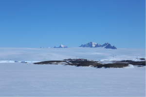 View over Mawson station and the ice plateau with its mountains in the background. Photo by Richard Youd.