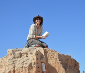 Emily holding sitting at the top of her site at Lake Mungo, holding one of her monolith samples.